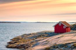 Una casa rossa su una scogliera di fronte al mare
