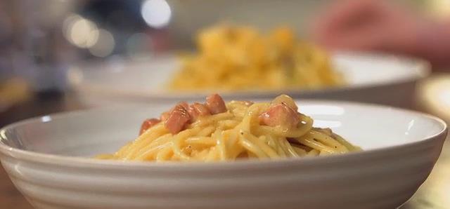 Due piatti bianchi uno con carbonara classica con pepe, pecorino e guanciale e l'altra vegetariana.