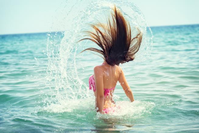 Ragazza con capelli al mare