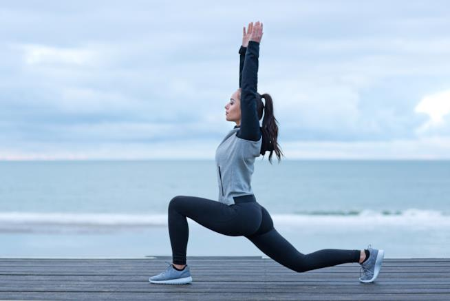 Una ragazza fa stretching su un pontile