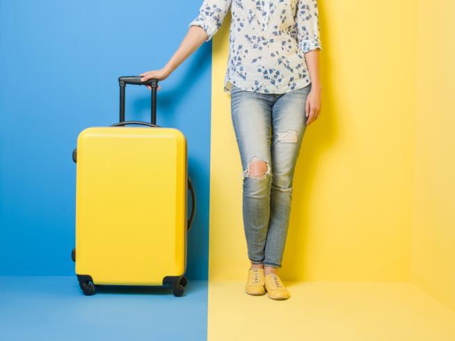 Ragazza con valigia gialla su fondo azzurro