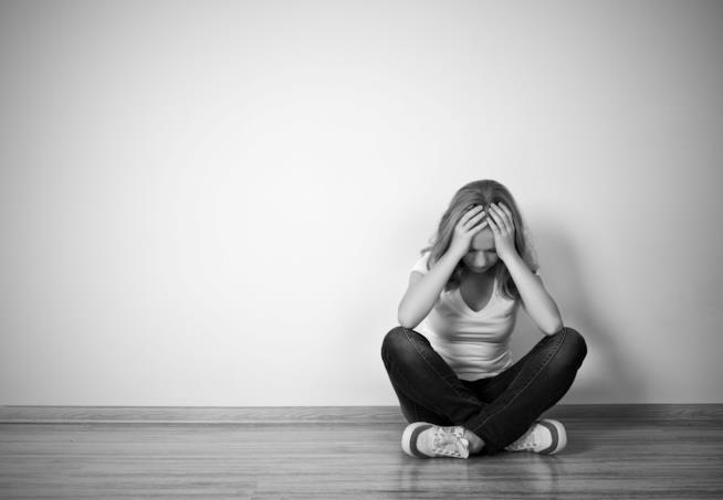 Una ragazza è seduta a terra depressa con la testa tra le mani