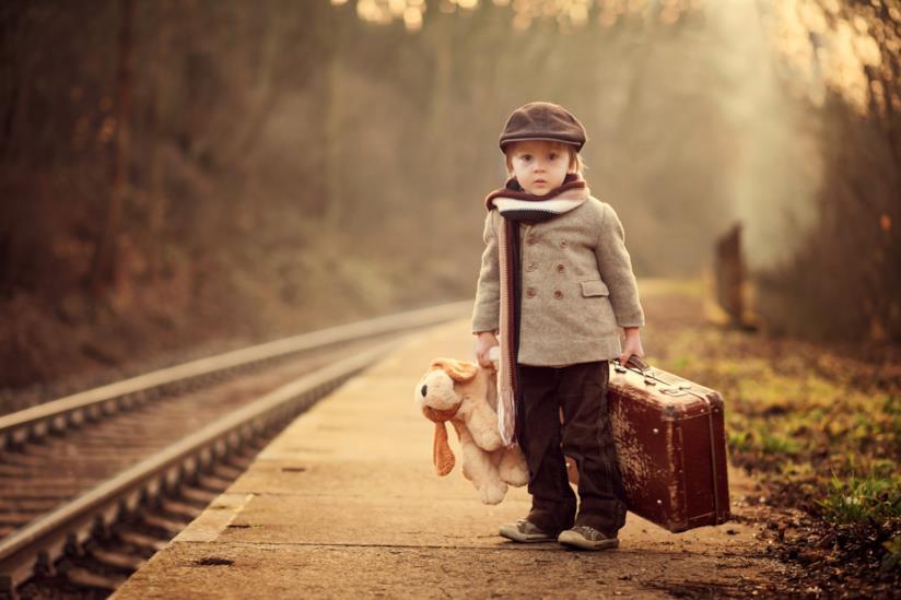 adorabile bambino con valigia e orsacchiotti alla fermata del treno