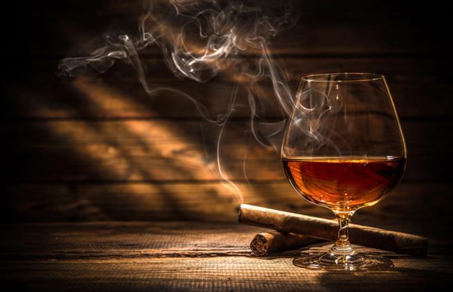 Primo piano di un bicchiere di whiskey e due sigari