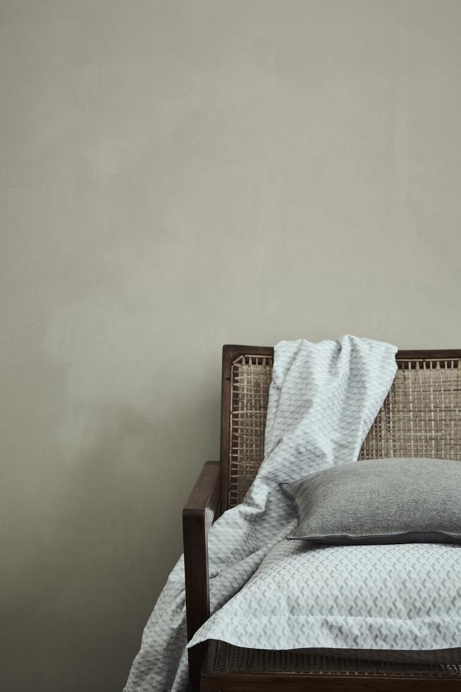 Poltrona in legno e midollino con coperta in cotone e cuscino con fodera in lana cotta