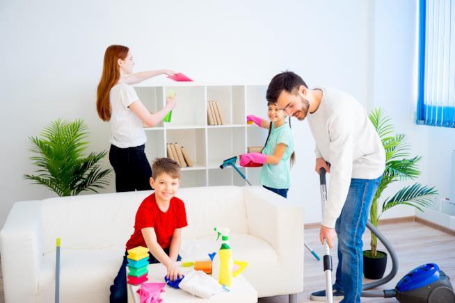 Papà, mamma e bambini, insieme a pulire casa