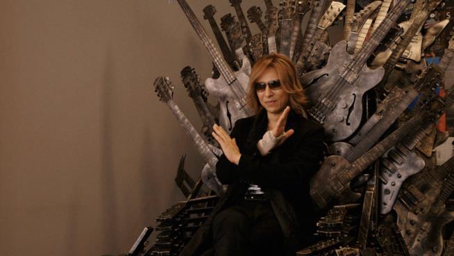 Yoshiki siede su un trono di chitarre