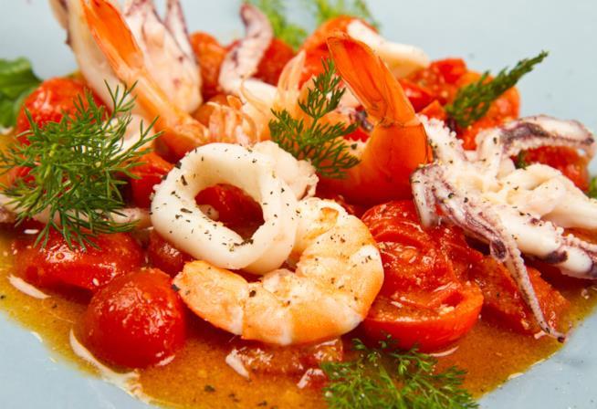 Primo piano della zuppa di pesce con pomodorini freschi, gamberi, polpo e calamari.