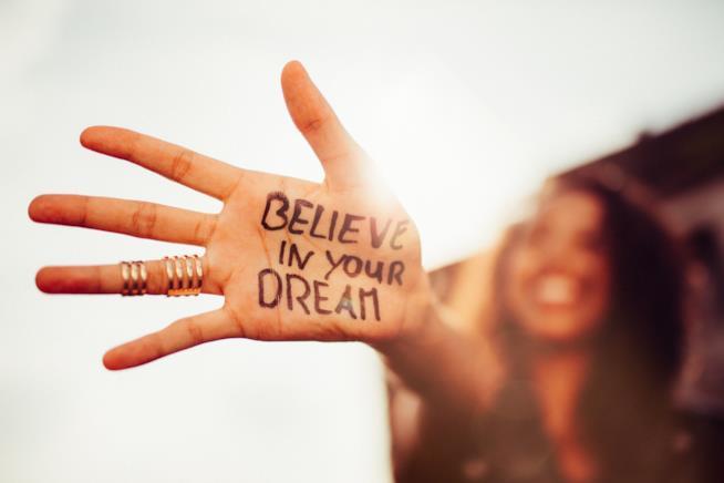 Una ragazza mostra una mano con la scritta credi nei tuoi sogni