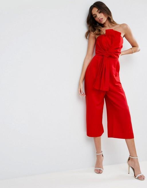 Modella indossa jumpsuit rosso con fiocco