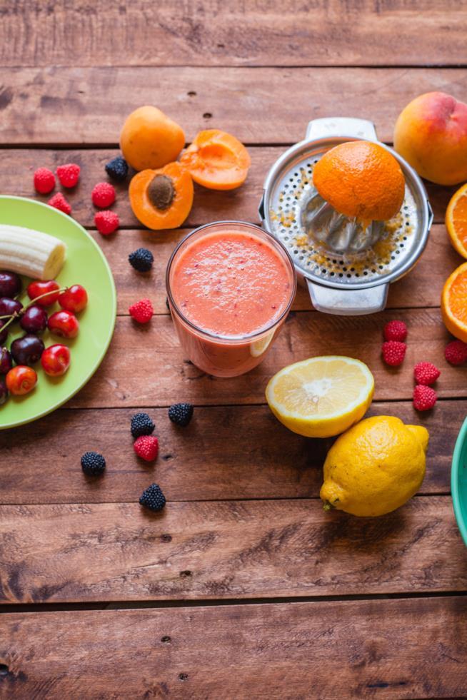inquadratura dall'alto, un piattino, un bicchiere e uno spremi aranciacon tanta frutta colorata intorno
