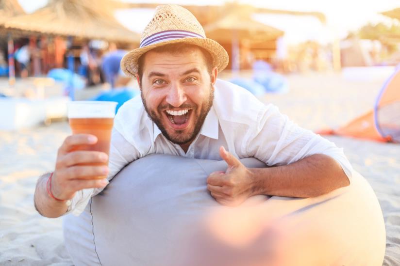 Un ragazzo sorridente in spiaggia pronto a bere un bicchiere di birra