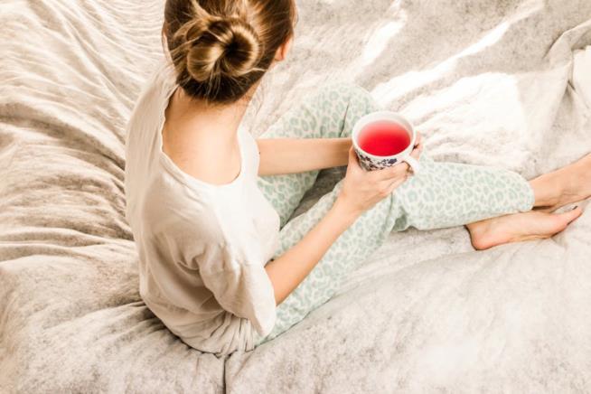 Ragazza a letto che beve un infuso