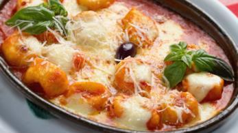 Primo piano di tegame con gnocchi di patate, passata di pomodoro, mozzarella e basilico