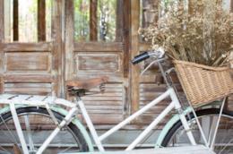 Bicicletta vintage davanti a una porta vetrata in legno naturale