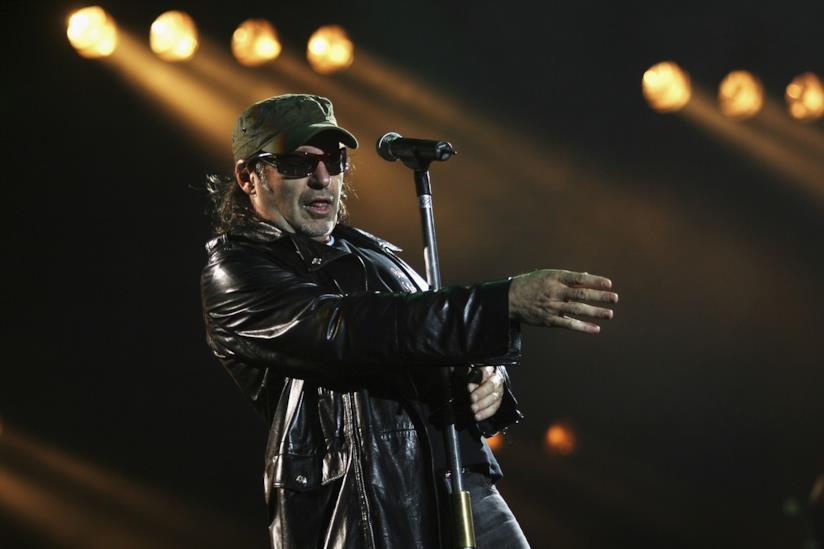 Vasco Rossi, in piedi, di fronte al microfono, con la giacca di pelle, un paio di occhiali da sole e un cappellino verde