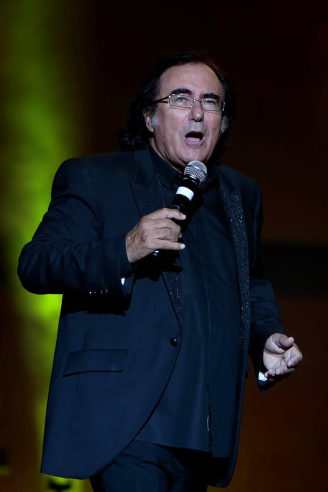 Al Bano, in nero, canta al microfono