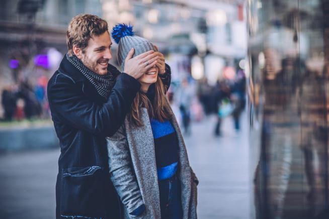 Un ragazzo copre gli occhi della sua fidanzata con le mani per farle una sorpresa