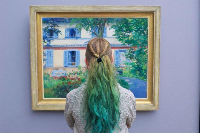 Una ragazza dai capelli biondi e verdi di fronte ad un quadro