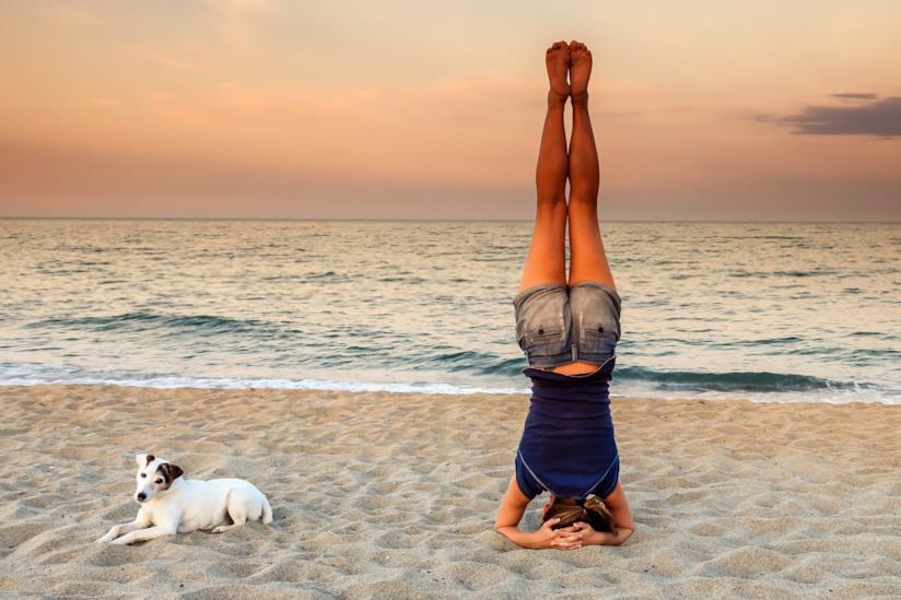 Una ragazza in spiaggia esegue la posizione sulla testa