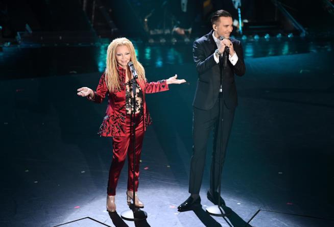 Patty Pravo in rosso e Briga in nero, in piedi, di fronte al microfono