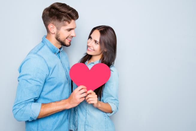 Giovane coppia tiene in mano un cuore
