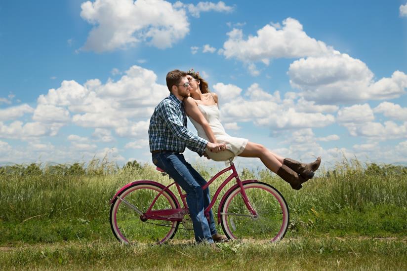 Ragazza seduta sul manubrio di una bicicletta bacia sulla guancia il fidanzato alla guida