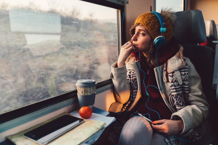 Ragazza viaggia in treno guardando dal finestrino