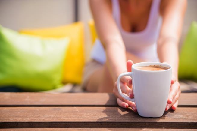 Una ragazza tiene una tazza di caffè tra le mani