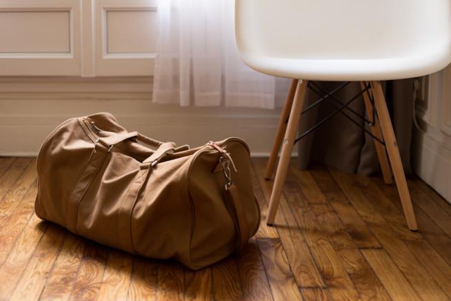 Una valigia chiusa vicino ad una sedia bianca.