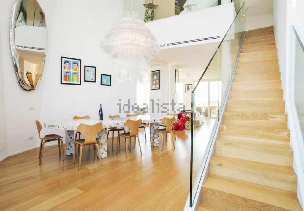 La scala in legno, un lungo tavolo e delle sedie in legno