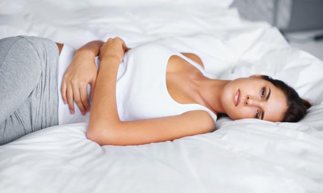 Ragazza a letto con il mal di pancia