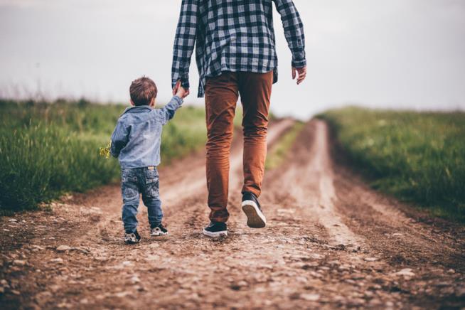 Un padre cammina tenendo per mano suo figlio