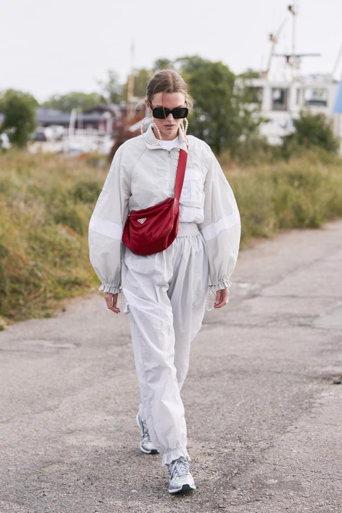 Tuta bianca con borsa a tracolla Prada