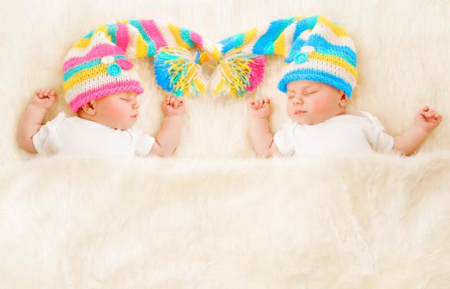 Due neonati gemelli dormono l'uno accanto all'altro