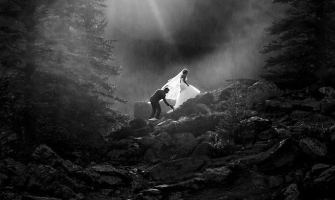 Una foto in bianco e nero di due sposi tra le rocce