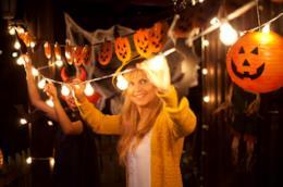 Una donna è intenta ad addobbare la casa per Halloween