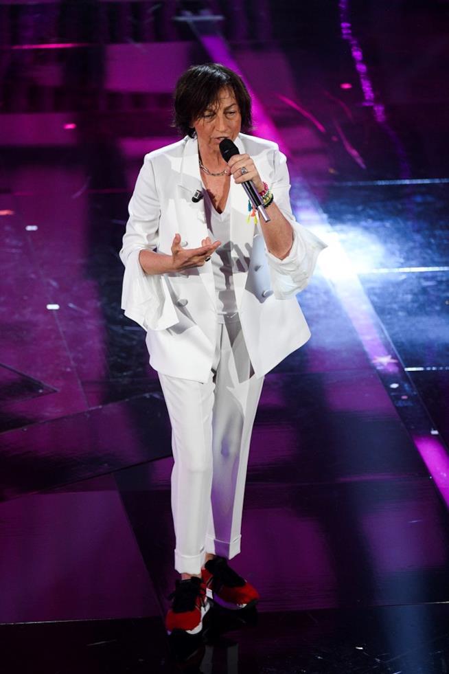 Gianna Nannini, vestita di bianco, con delle scarpe rosse, canta in piedi al microfono