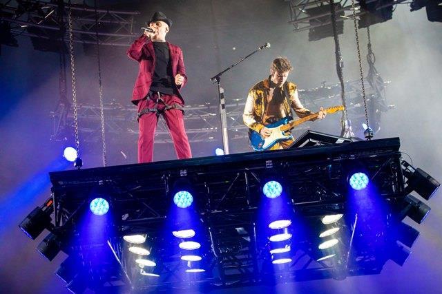 J-Ax in rosso, Fedez con la giacca aperta, che suona la chitarra, entrambi su un palco sollevato da terra