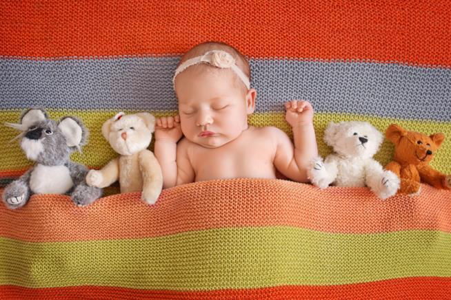 Un neonato dorme con i peluche