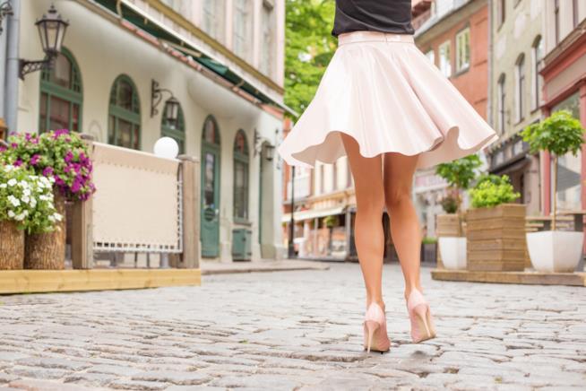 inquadratura di spalle di una donna a metà busto, indossa scarpe rosa con il tacco e gonna che svolazza mentre cammina su una strada