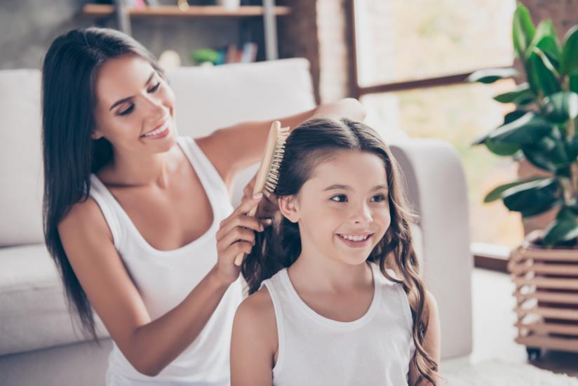 Mamma che realizza un'acconciatura per bambina con capelli lunghi