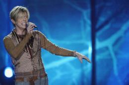 David Bowie, in piedi, canta al microfono