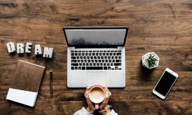 Primo piano di una scrivania con computer e smarthphone