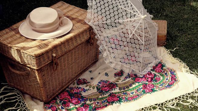 Cestino da picnic con ombrellino parasole su una stuola