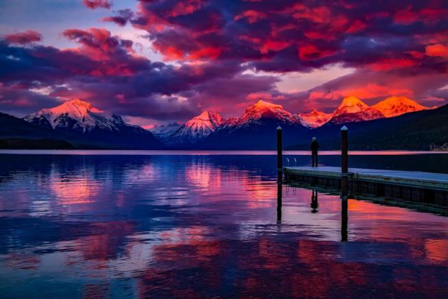 Ragazzo su un pontile osserva un paesaggio montuoso al tramonto