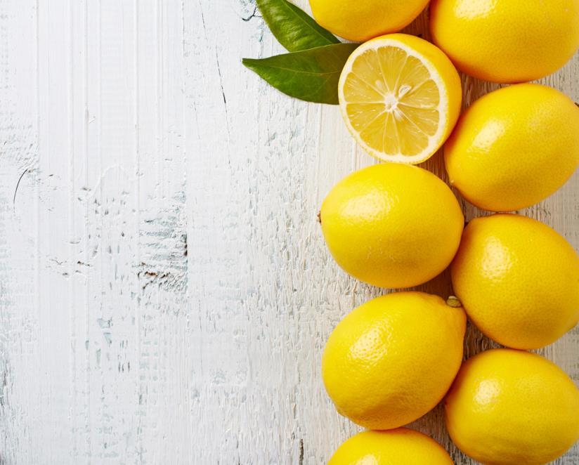9 limone messi in fila, uno aperto a metà, posati su un tavolo grigio