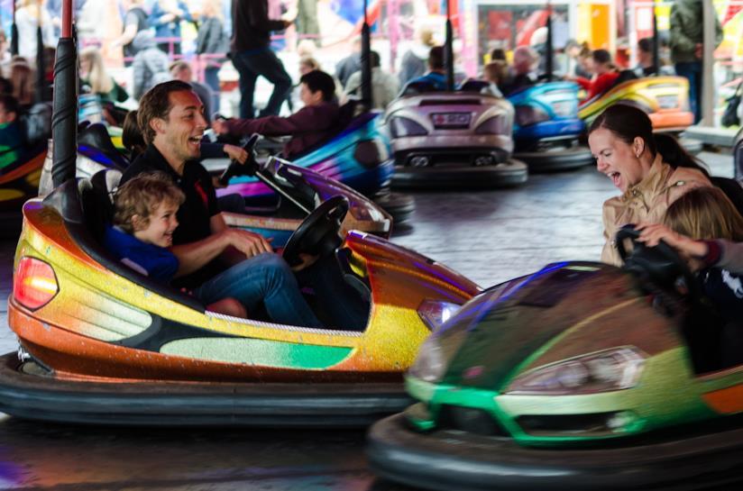 Un uomo, una donna e due bambini ridono agli autoscontri