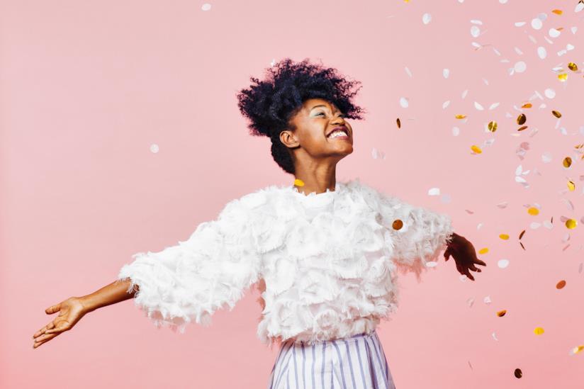Una ragazza con la maglia bianca che sorride con le braccia aperte.