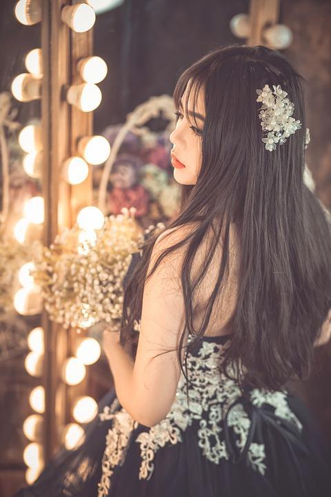 Una ragazza in posa accanto ad uno specchio